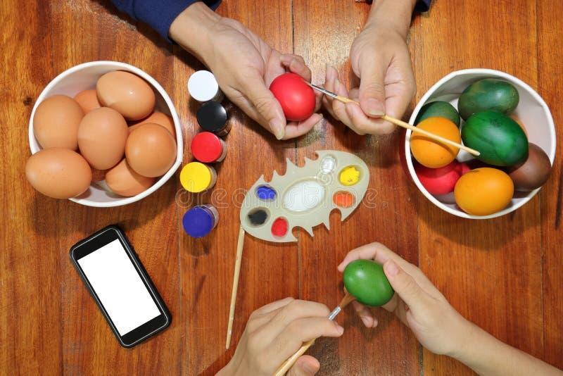 De handen van familieleden hebben een goede tijd met het kleuren van eieren voor Pasen-dag voorbereidingen treffen stock afbeelding