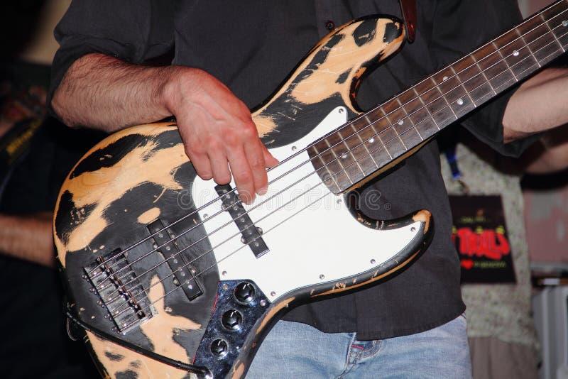 De handen van de gitarist maken de koorden van het instrument trillen stock fotografie