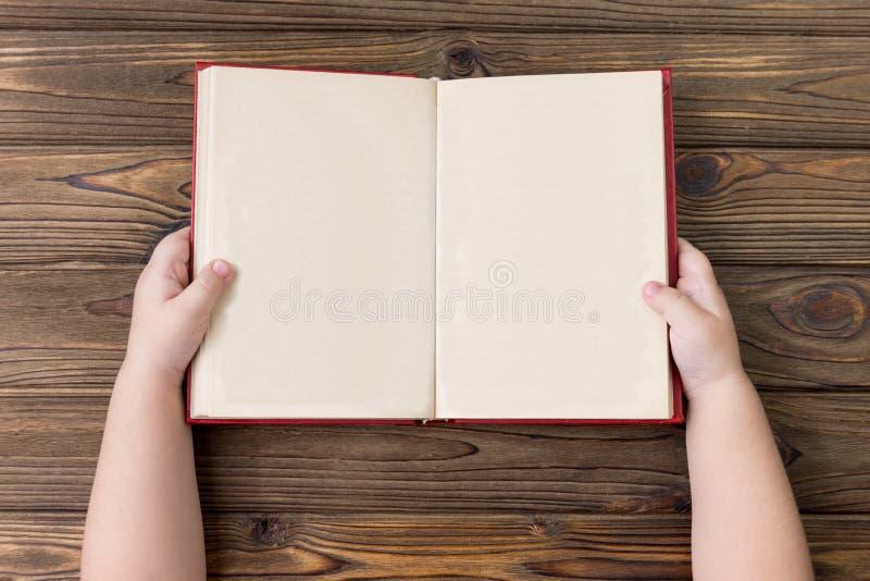 De handen van het kind houden een open boek met schone bladen van pagina's stock foto's