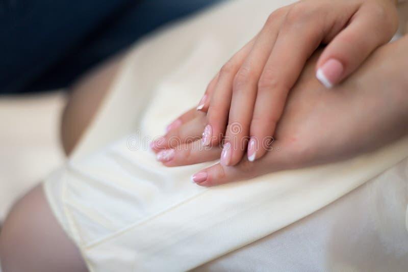 De handen van het meisje met huwelijksmanicure Close-upvrouw die de handen van haar handenbruid met een aardige manicure tonen royalty-vrije stock afbeeldingen