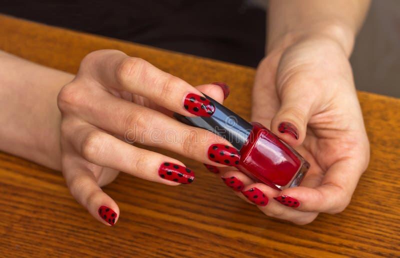 De handen van het meisje met rood nagellak die een fles met vernis houden stock foto's