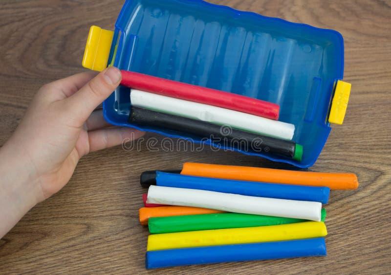 De handen van het meisje nemen de multi-colored klei stock afbeelding