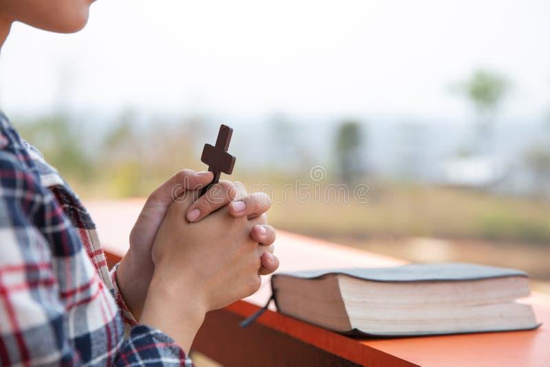 De handen van de jonge het bidden vrouw met houten dwars en Heilige Bijbel Het concept van de godsdienst Boek en kruis royalty-vrije stock fotografie