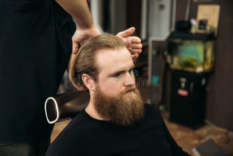 De handen van jonge kapper die tot kapsel maken aan de aantrekkelijke gebaarde mens in herenkapper royalty-vrije stock foto's