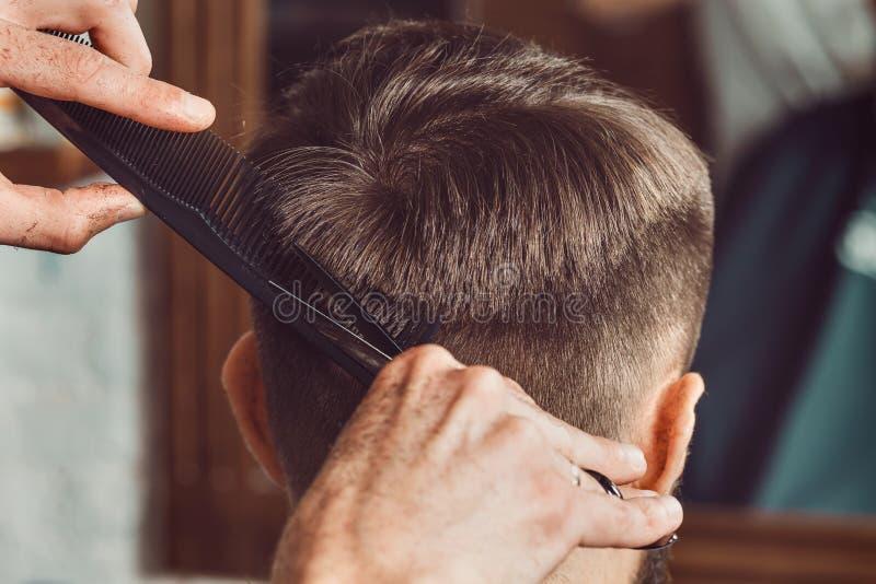 De handen van jonge kapper die tot kapsel maken aan de aantrekkelijke mens in herenkapper royalty-vrije stock afbeelding