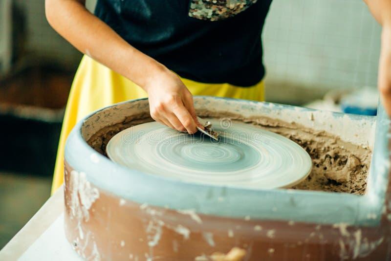 De handen van jonge pottenbakker, sluiten omhoog handen gemaakt tot kop op aardewerkwiel royalty-vrije stock foto's