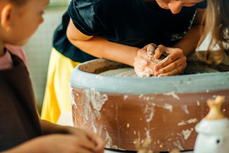 De handen van jonge pottenbakker, sluiten omhoog handen gemaakt tot kop op aardewerkwiel stock foto