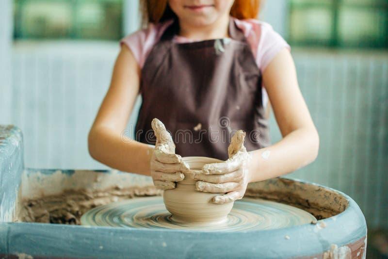 De handen van jonge pottenbakker, sluiten omhoog handen gemaakt tot kop op aardewerkwiel stock foto's