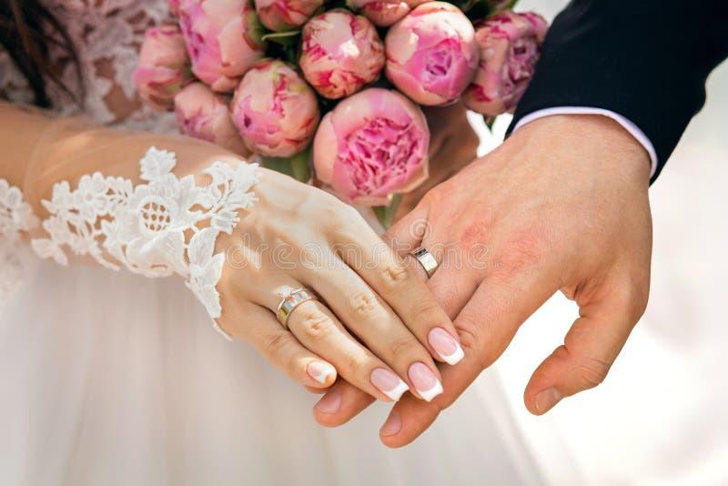 De handen van de jonggehuwden met ringen op de vingers, naast een boeket met roze pioenen, de bruid en de bruidegom houden handen royalty-vrije stock afbeelding