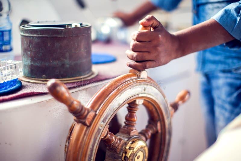 De handen van de kapitein en de een havendiensten van de stuurwielboot overzees en reisconcept stock foto's