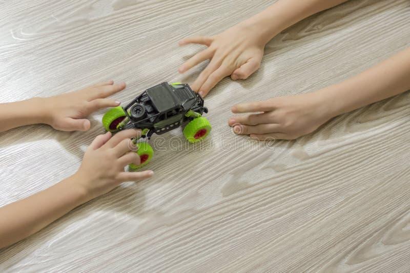 De handen van kinderen en een stuk speelgoed auto royalty-vrije stock fotografie