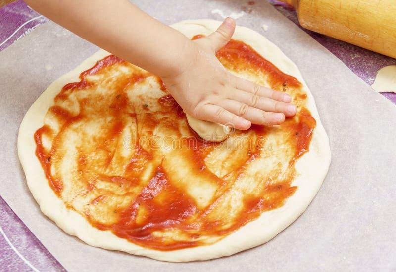 De handen van kinderen kneden het pizzadeeg op een siliconemat royalty-vrije stock fotografie