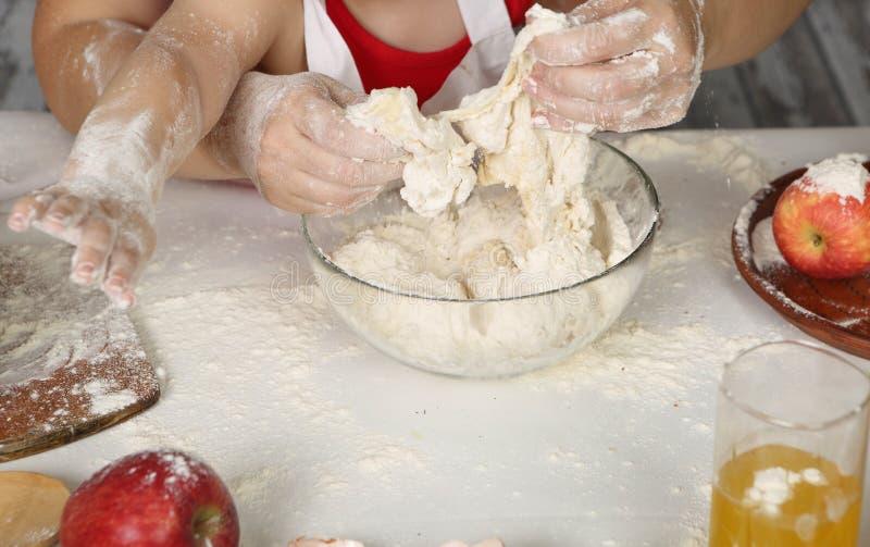 De handen van kinderen maken pastei uit gebakje royalty-vrije stock foto