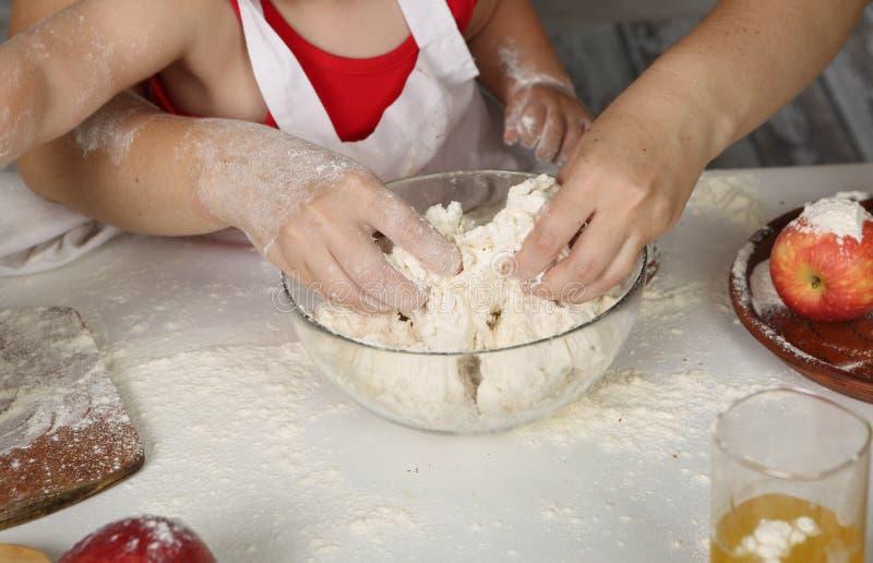 De handen van kinderen maken pastei uit gebakje royalty-vrije stock fotografie