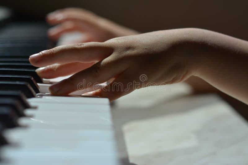 De handen van kinderen op de pianosleutels stock afbeelding