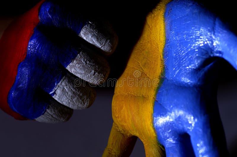 De handen van kinderen zijn geschilderde kleur van een vlag van de Oekraïne en Rusland De Oekraïne en Rusland stock foto