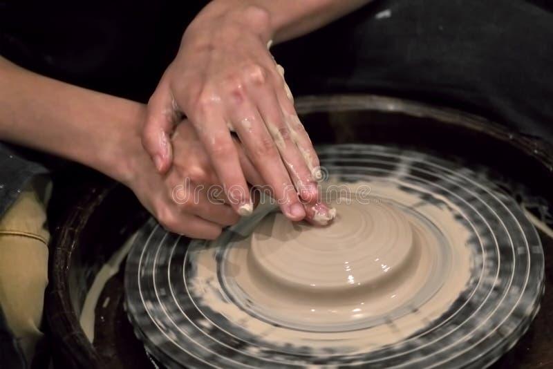 De handen van de meester die met klei aan een wiel van de pottenbakker werken, c royalty-vrije stock afbeelding