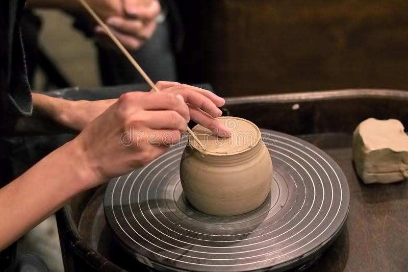 De handen van de meester die met klei aan een wiel van de pottenbakker werken, c royalty-vrije stock afbeeldingen