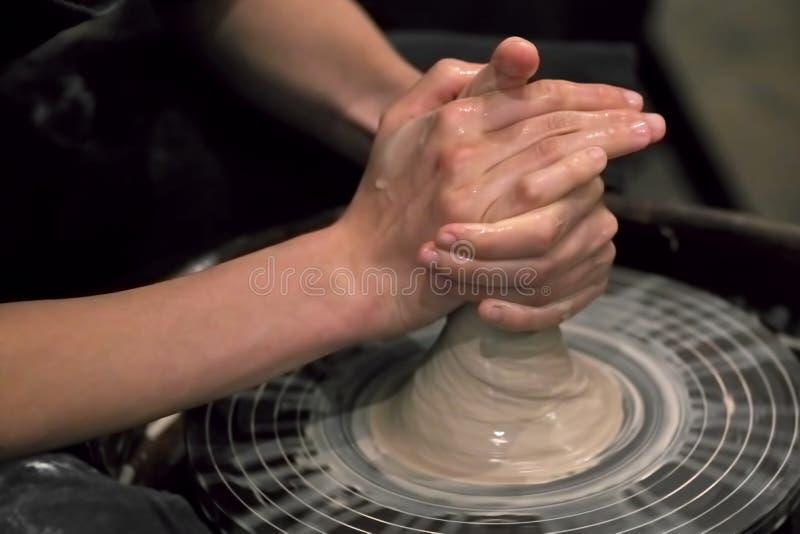 De handen van de meester die met klei aan een wiel van de pottenbakker werken, c stock foto's