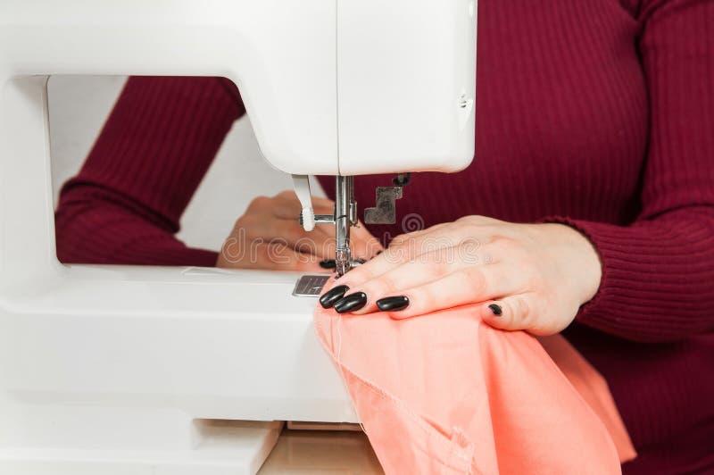 De handen van meisje naait op de naaimachine Ge?soleerdj op witte achtergrond royalty-vrije stock foto's