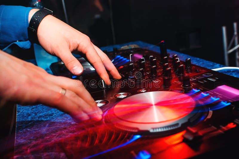 De handen van de de mengelingsmuziek van DJ op professioneel muziekmateriaal voor CDs met knopen en controlemechanismen royalty-vrije stock afbeelding