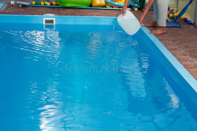 De handen van mensen gieten lichte vloeistof van een plastic tank in een pool, in water chemische waterreiniging, alkali unsanita stock foto