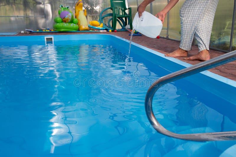 De handen van mensen gieten lichte vloeistof van een plastic tank in een pool, in water chemische waterreiniging, alkali unsanita stock foto's