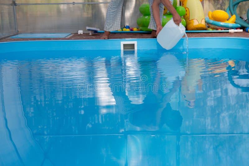 De handen van mensen gieten lichte vloeistof van een plastic tank in een pool, in water chemische waterreiniging, alkali unsanita stock afbeeldingen