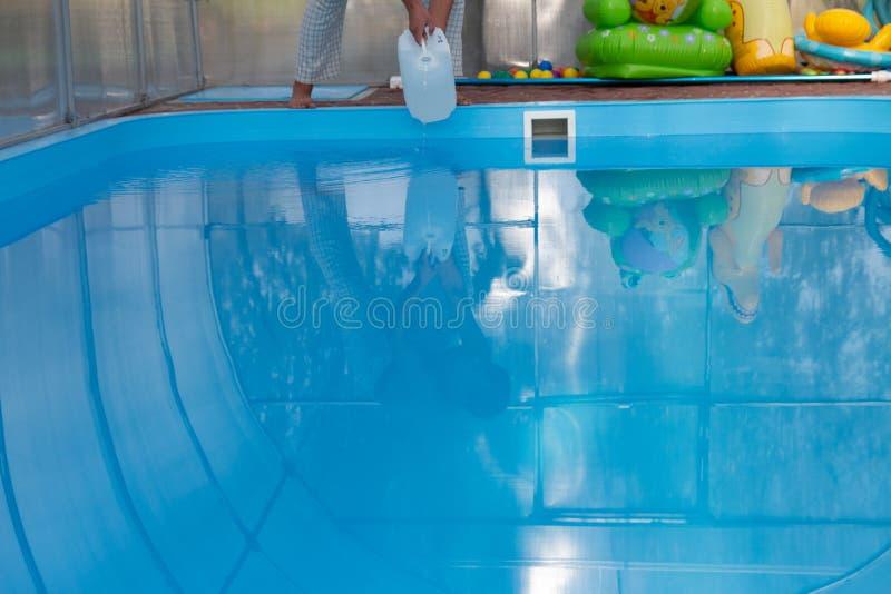 De handen van mensen gieten lichte vloeistof van een plastic tank in een pool, in water chemische waterreiniging, alkali unsanita stock afbeelding