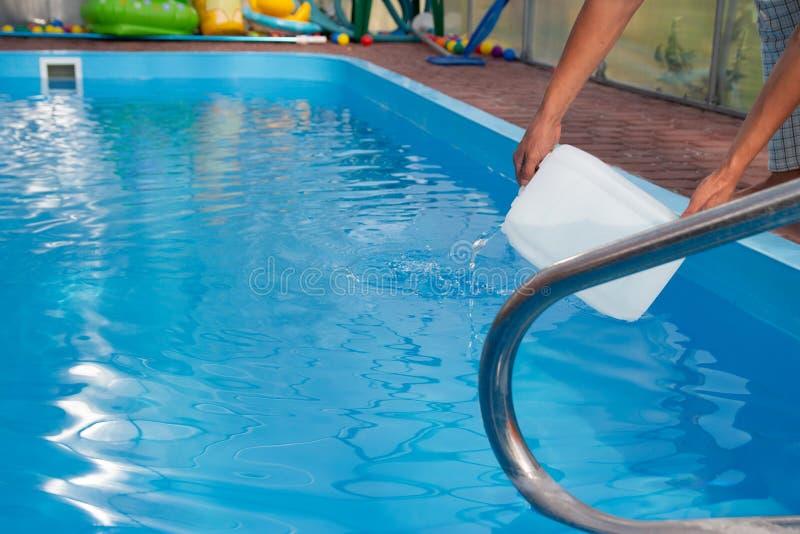 De handen van mensen gieten lichte vloeistof van een plastic tank in een pool, in water chemische waterreiniging, alkali unsanita royalty-vrije stock foto