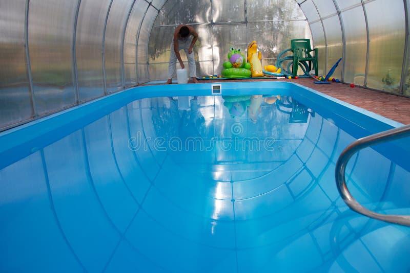 De handen van mensen gieten lichte vloeistof van een plastic tank in een pool, in water chemische waterreiniging, alkali unsanita royalty-vrije stock afbeeldingen