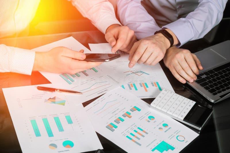 De handen van mensen met calculator en telefoon op de achtergrond van de documenten op de lijst stock afbeelding