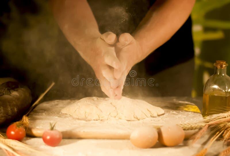 De handen van de mensenbakker, het kneden voorbereidingsdeeg die en het maken van brood mengen zich royalty-vrije stock afbeelding