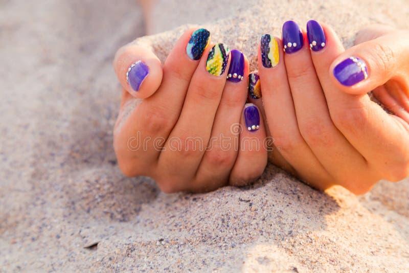 De handen van mooie vrouwen met een professionele manicure op het zand royalty-vrije stock afbeelding