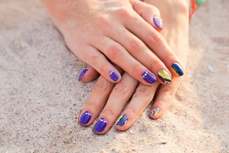 De handen van mooie vrouwen met een professionele manicure op het zand stock foto's
