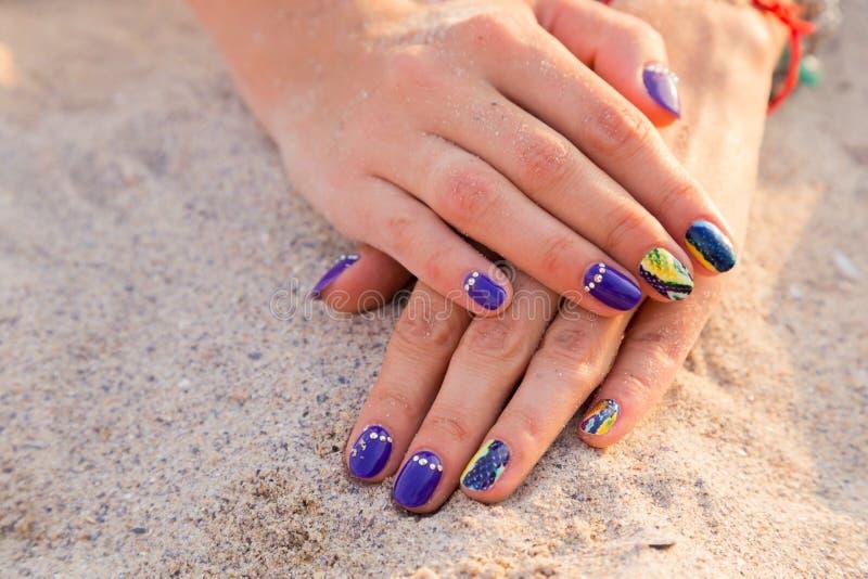 De handen van mooie vrouwen met een professionele manicure op het zand royalty-vrije stock fotografie