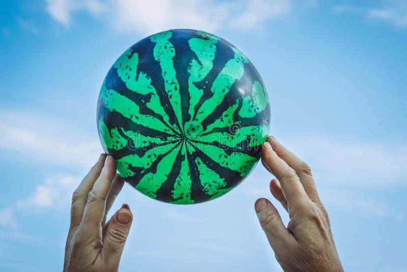 De handen van de oude man die een bal in de vorm van watermeloen houden stock afbeeldingen