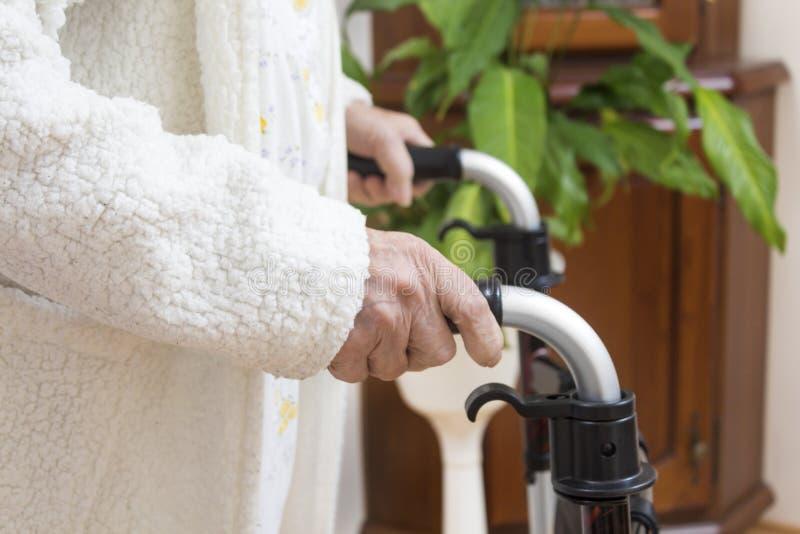 De handen van de oude vrouw houden het handvat van het balkon De oma in een witte peignoir leunt op de rehabilitatiebedelaars royalty-vrije stock fotografie