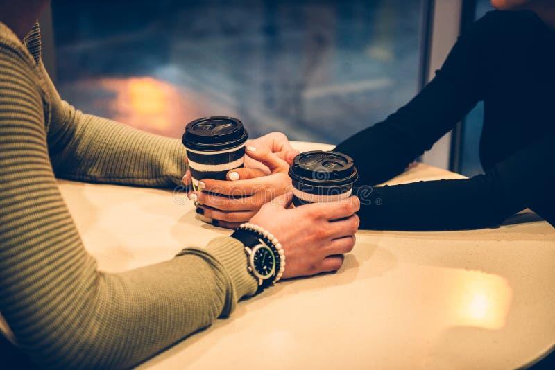 De handen van de paarholding en het drinken koffie in de koffie stock afbeelding