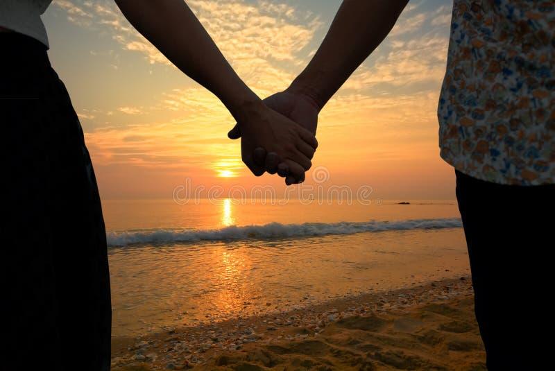 De handen van de paarholding en mooie zonsondergang op het strand stock foto