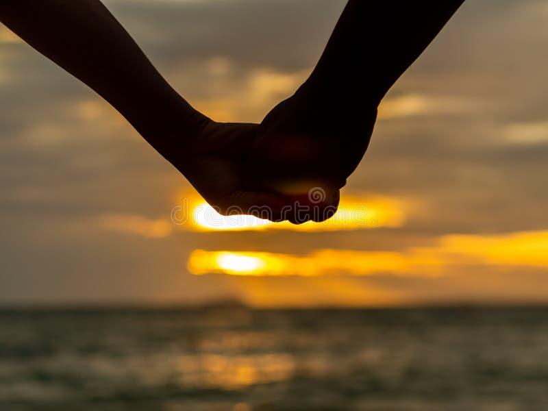 De handen van de paarholding op mooie zonsondergangachtergrond bij het strand royalty-vrije stock foto's