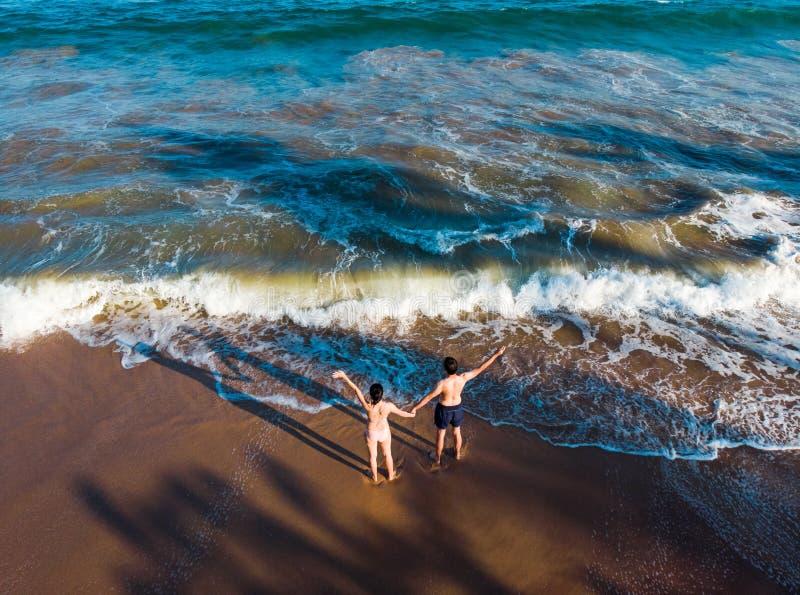 De handen van de paarholding op de strandantenne stock foto's