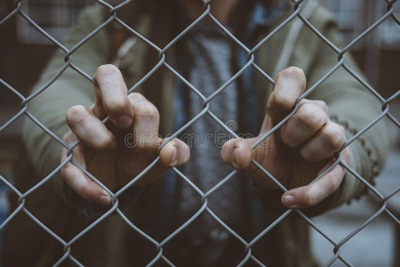 De handen van de persoon op een ketting verbonden omheining stock afbeelding