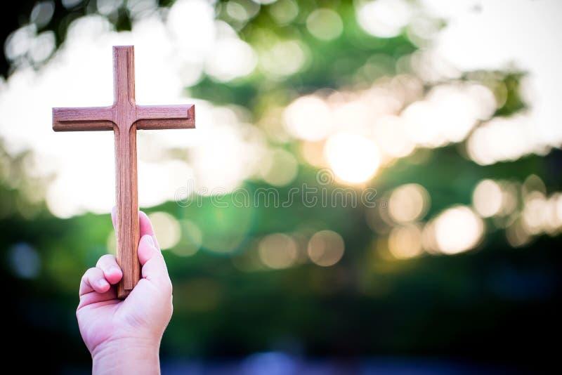 de handen van de persoonspalm om heilig kruis, kruisbeeld te houden om te aanbidden stock fotografie