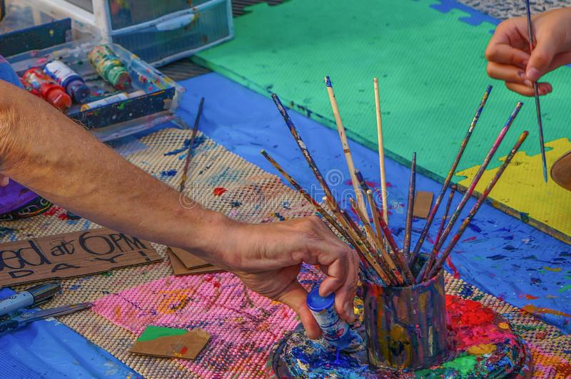 De handen van twee verschillende mensenkunstenaars dichtbij de schotel met mok van borstels op het tapijt giet fles van blauwe ve stock foto's