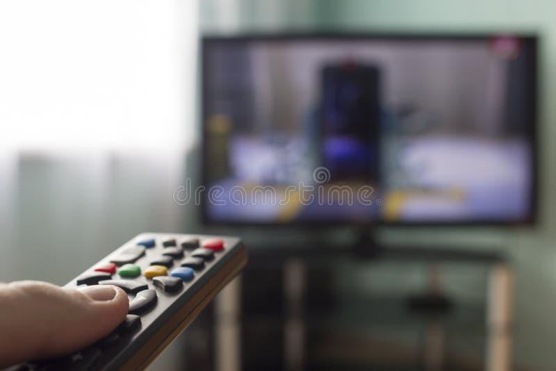 In de handen van ver van TV, op de achtergrond komt de TV-televisie stock foto's