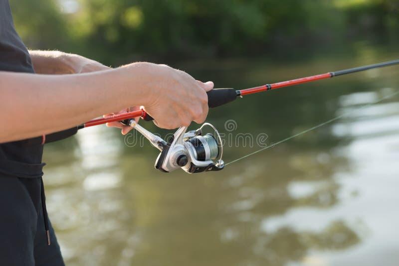 De handen van de visser houden een visserij spinnend over het water terwijl visserij stock foto