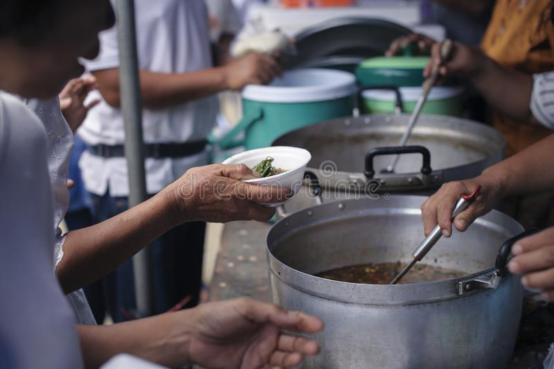De handen van vluchtelingen zijn geholpen door liefdadigheidsvoedsel honger verminderen: Het voeden Concepten: De hand bood aan o stock foto
