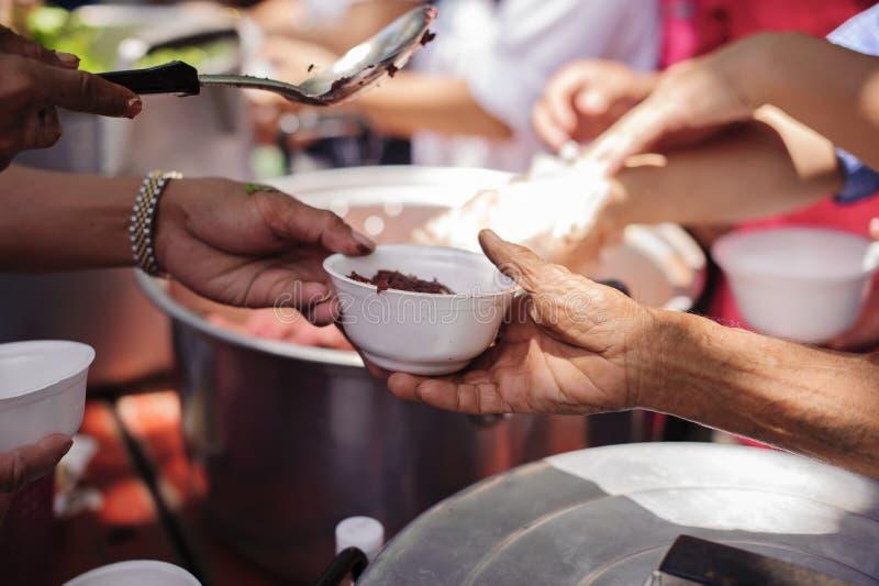 De handen van vluchtelingen zijn geholpen door liefdadigheidsvoedsel honger verminderen: Het voeden Concepten: De hand bood aan o royalty-vrije stock fotografie