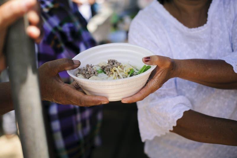 De handen van vluchtelingen zijn geholpen door liefdadigheidsvoedsel honger verminderen: Het voeden Concepten: De hand bood aan o royalty-vrije stock foto's